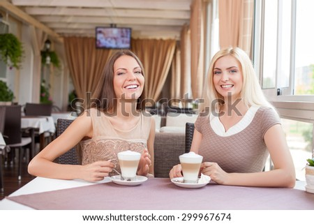 Pretty women are sitting at the table and drinking latte in cafe. They are spending time with joy. The women are smiling and looking at the camera with enjoyment - stock photo