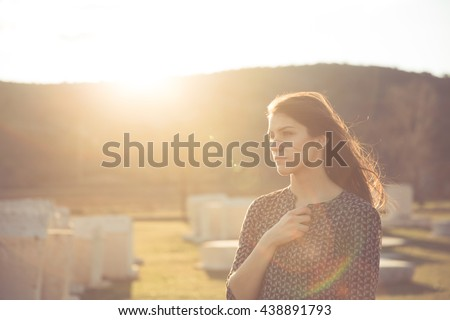 Pretty women grieving for a lost love. Sad separation of two lovers under sunset. Escape to nature after a depressive day. Pensive, melancholic visit to the grave of a loved person.