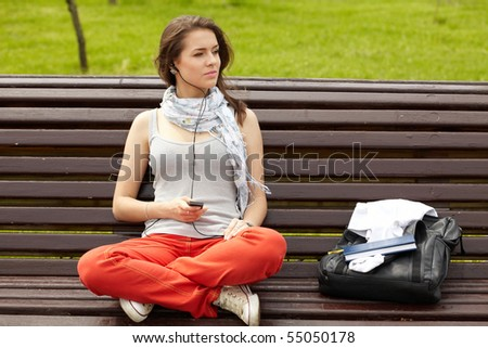pretty women in the park listening music - stock photo