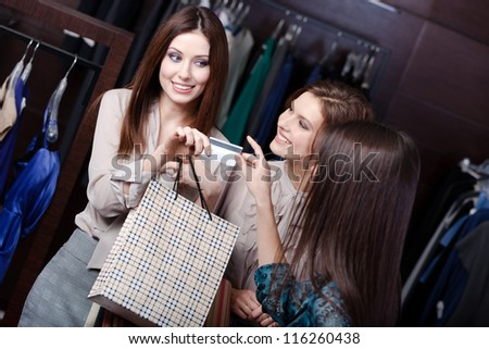 Pretty women pay with credit card and take away purchases - stock photo