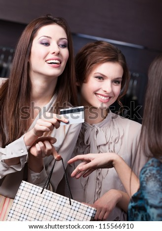 Pretty women settles an account with credit card at the store - stock photo