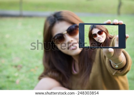 pretty women wear eyeglass smile use smart phone mobile take self picture selfie in park