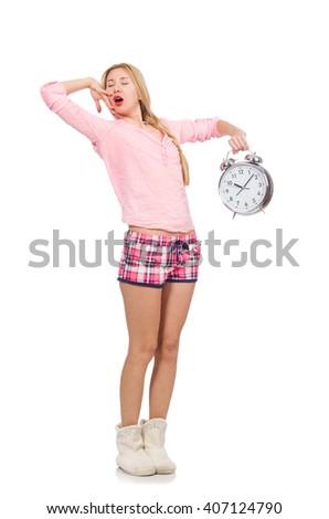 Pretty yawning girl holding alarm-clock isolated on white - stock photo