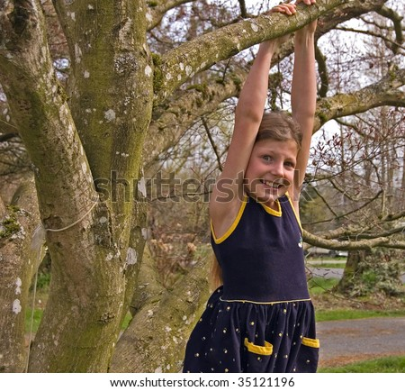 Pretty 8 year old girl is hanging from a tree in a navy blue dress.  She has a worried facial expression. - stock photo