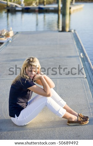 Pretty 17 year old teenage girl sitting alone on dock by water - stock photo