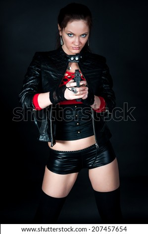 Pretty young adult woman with pistol ready to shot on black background - stock photo