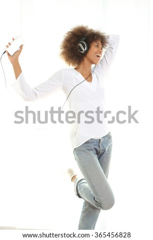 Pretty young african american girl listening music from her mobile phone and dancing. Standing against white background. - stock photo
