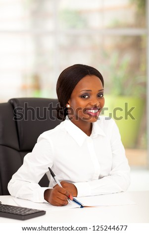 pretty young african american office worker by her desk
