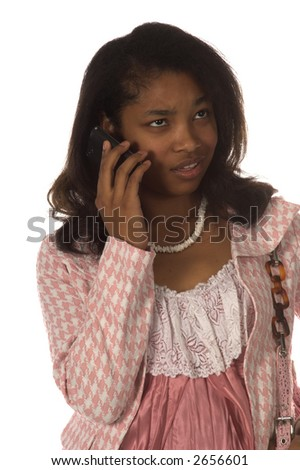 Pretty young African American woman dressed in a pink herringbone business suit talking on a cell phone with a upset expression on her face