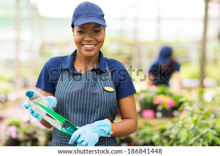 pretty young african gardener portrait in greenhouse - stock photo