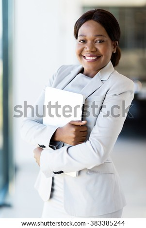 pretty young african office worker holding laptop computer - stock photo