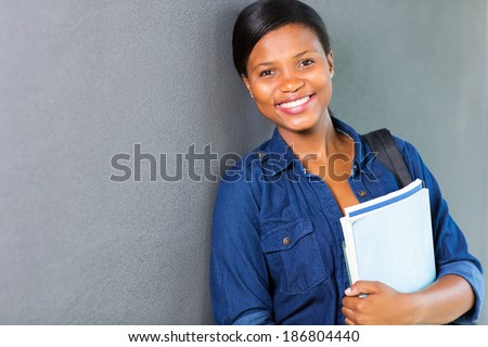 pretty young african university girl standing against the wall - stock photo