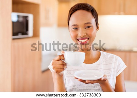 pretty young african woman drinking coffee in kitchen