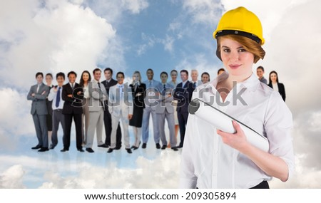 Pretty young architect smiling at camera against blue sky with white clouds and business people - stock photo