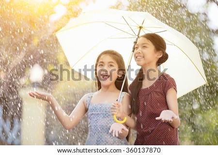 Pretty young asian girl in the rain with umbrella - stock photo