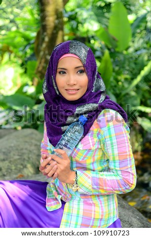 Pretty young Asian Muslim woman with drink mineral water in the bottle