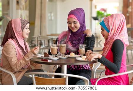 Pretty young Asian Muslim women discussion while having lunch at coffee shop - stock photo