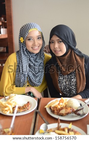 Pretty young Asian Muslim women having lunch at coffee shop - stock photo