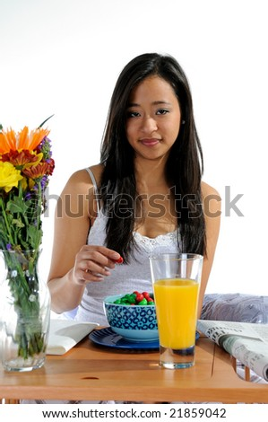 Pretty young Asian woman eating candy - breakfast in bed