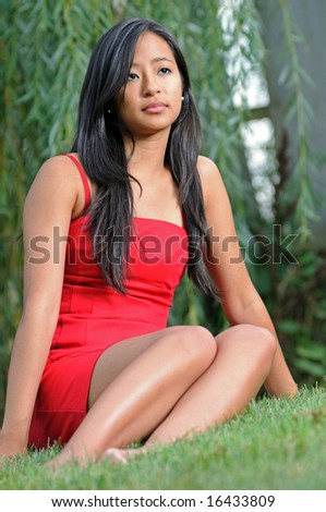 Pretty young Asian woman sitting in red dress