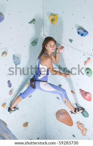 Pretty, young, athletic girl climbing on an indoor rock-climbing wall