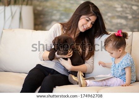 Pretty young babysitter looking after a puppy and a little girl - stock photo