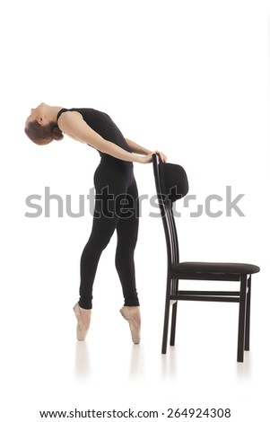 Pretty young ballerina posing with chair on white background - stock photo