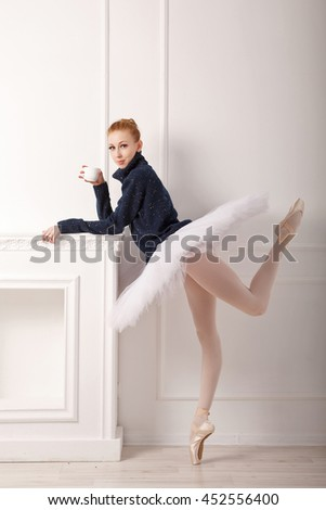 Pretty young ballerina standing by the fireplace, drinking tea. A girl wearing a tutu and black sweater. - stock photo
