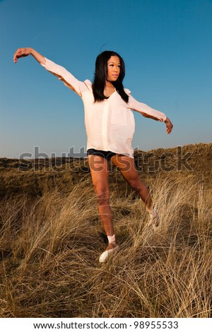 Pretty young black woman posing in dune landscape with clear blue sky. Enjoying outdoors. Wearing ballerina shoes.