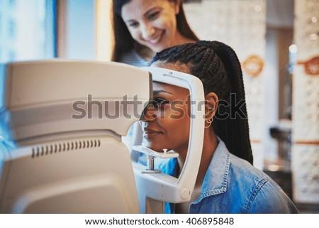 Pretty young black woman presses her forehead to optical machine to take eye exam - stock photo