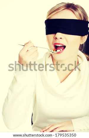 Pretty young blindfold woman holding spoon with pile of pills - stock photo