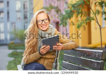 Pretty young blond caucasian smiling woman with grey scarf and glasses using tablet computer sitting on the wooden bench outdoor - stock photo