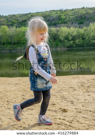 Pretty young blond girl running on a sandy beach alongside a watercourse smiling as she enjoys the freedom and sunshine