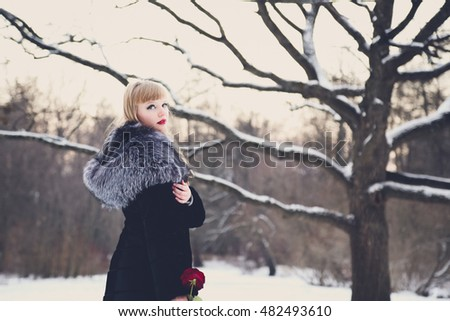 Pretty young blond woman in a black coat with a bright make-up and with a rose in hand in winter in a park