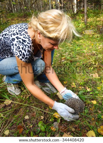 Pretty young blond woman in autumn forest hedgehog found - stock photo