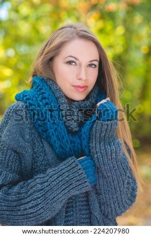 Pretty Young Blond Woman in Thick Gray Knit Jacket During Autumn Season. Looking at Camera. Captured Outdoor.