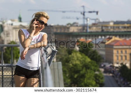 Pretty young blond woman talking on mobile phone outdoors in the city. - stock photo
