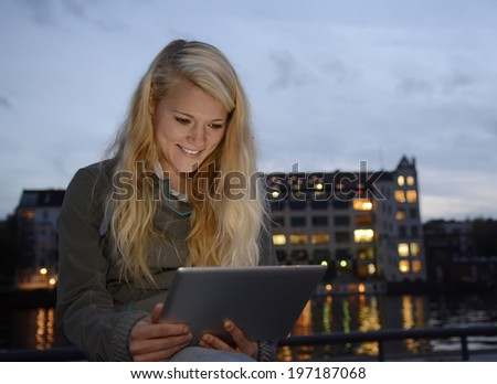 pretty young blond woman with tablet computer in the city - stock photo