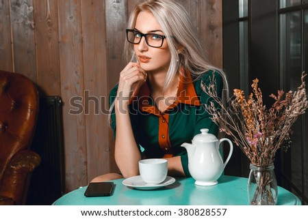 Pretty young blonde business woman with cup of tea in cafe looking at camera. Business woman in cafe. Business concept. Business after hours.