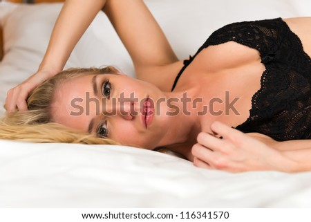 Pretty young blonde dressed in black lingerie - stock photo