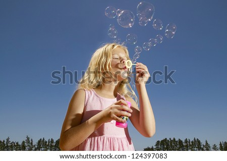 Pretty young blonde girl in a pink frock standing against a blue sky blowing bubbles