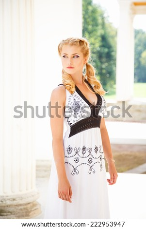 Pretty young blonde girl near gorgeous house with columns in a summer