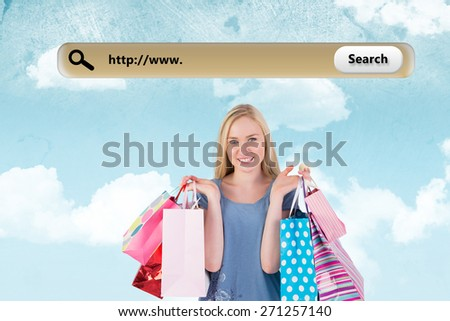Pretty young blonde holding shopping bags against painted sky - stock photo