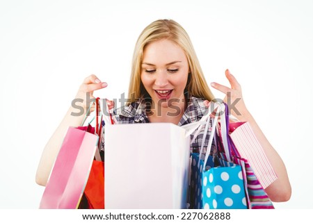 Pretty young blonde holding shopping bags on white background