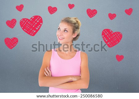 Pretty young blonde in pink looking up with arms crossed against grey - stock photo