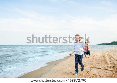 Pretty young blonde mother and little cute girl playing at the beach. Travel and Vacations.