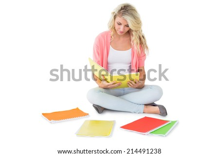 Pretty young blonde sitting and studying on white background - stock photo