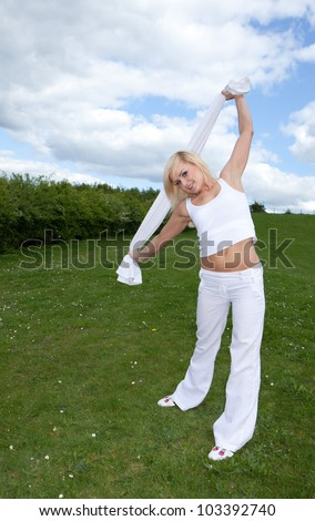 Pretty young blonde stretching arms on a field - stock photo