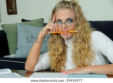 Pretty young blonde student biting pencil