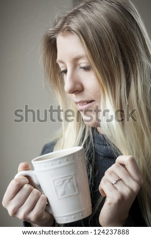 Pretty young blonde woman drinking her morning coffee.